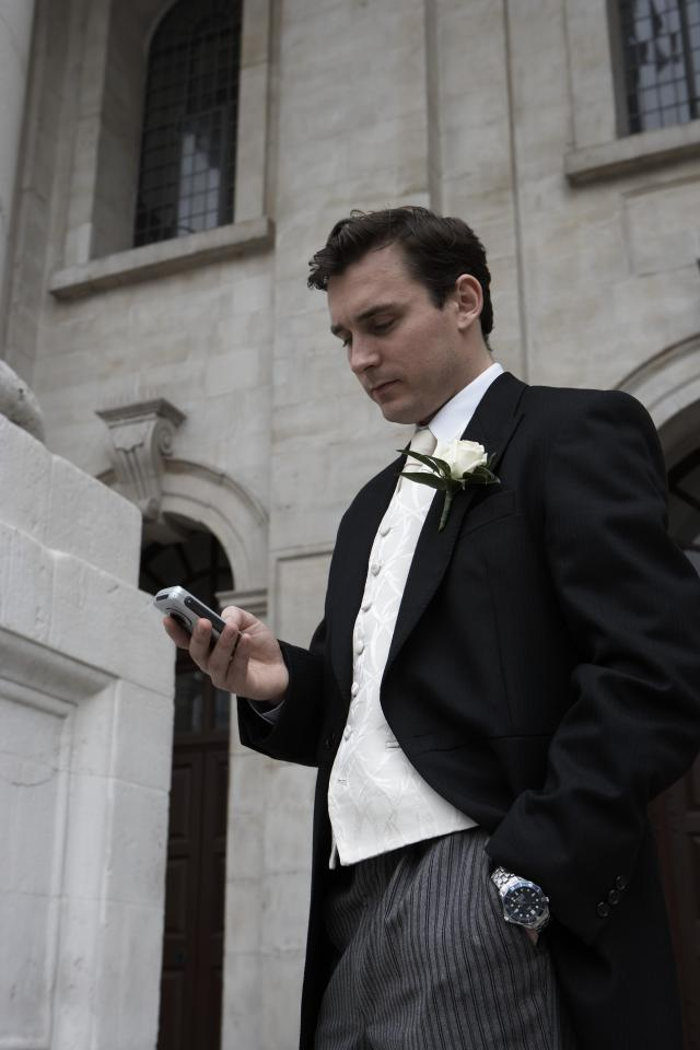 Groom standing outside looking at mobile phone, hand in pocket